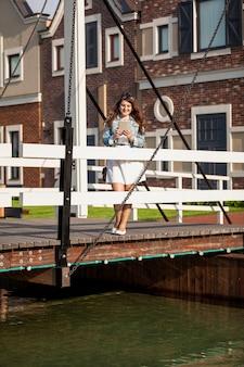 ヨーロッパの木製の橋の上に立っている美しい女性