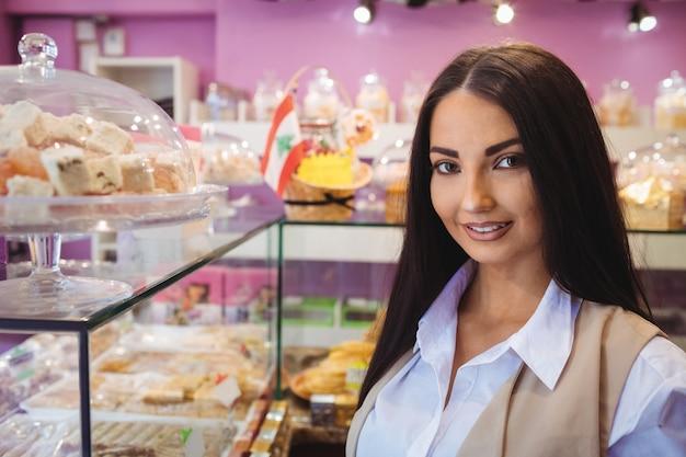 Bella donna in piedi in un negozio di dolci turchi