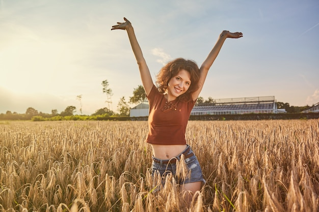 A beautiful woman standing on wheat field in summer