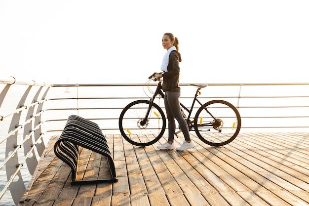 Красивая женщина, стоящая с велосипедом на променаде, во время восхода солнца над морем