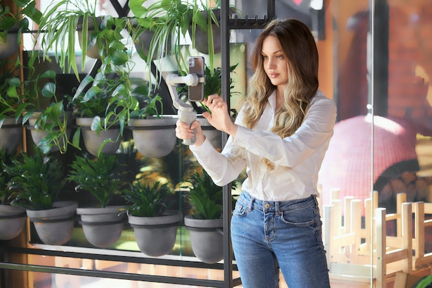 Beautiful woman standing with selfie stick in cafe