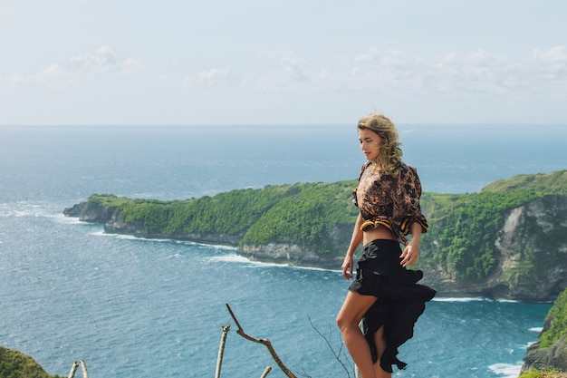 Beautiful woman stands on a cliff on the background of the sea and rocks in a windy day