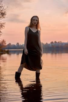 아름 다운 여자 일몰 연못에 물에 서