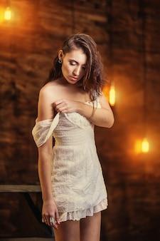 Красивая женщина стоит на деревянной лестнице в студии, поправляет платье, на фоне деревянной стены с горизонтальным воздушным шаром освещения.
