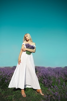美しい女性がラベンダーの牧草地に立っています。