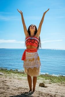 Красивая женщина стоит на пляже и поднимает руки в воздух