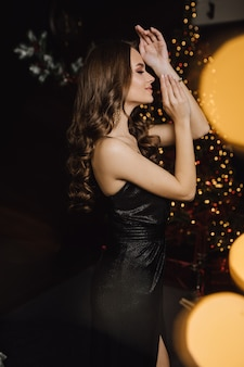 Beautiful woman stands sideway on a christmas tree