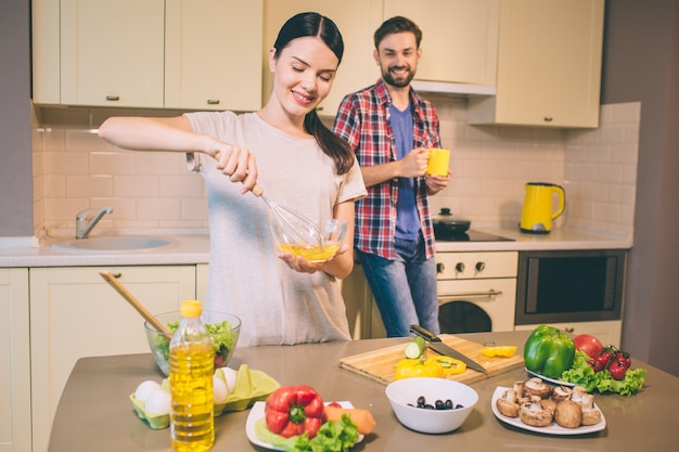Beautiful woman stands and smashes eggs in glass bowl. she looks at it and smile. guy stands behind her.