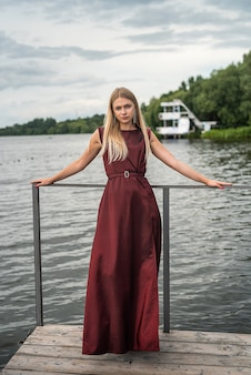 Beautiful woman stands wearing long dark red dress at nature. travel concept.