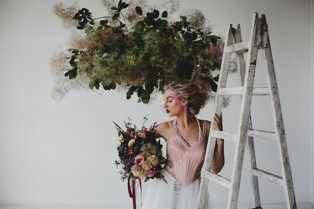 Beautiful woman stands with a bouquet among hanging laundry in the room