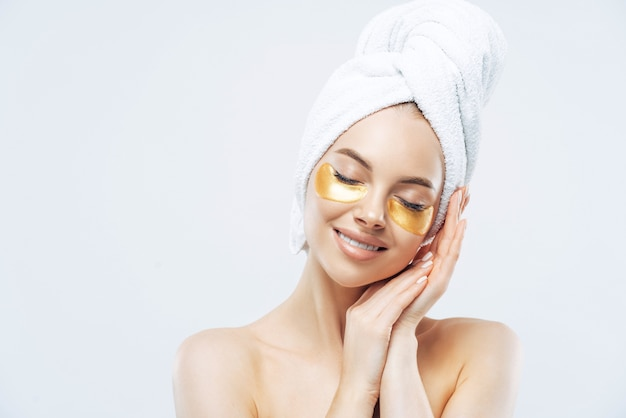 Beautiful woman stands with closed eyes, has soft healthy skin, leans at hands near face, smiles gently, wears golden patches to reduce puffiness under eyes, stands shirtless, wears towel, takes bath
