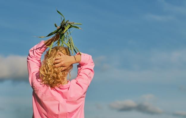 美しい女性は、小麦の頭の耳の上に両手で、フレームに背を向けて立っています。雲のある青い空、コピースペースのあるセレクティブフォーカス、バナーや背景のアイデア
