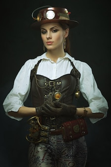 Beautiful woman steampunk. posing with the clock