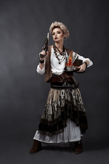Beautiful woman in steampunk style costume with hat and handgun