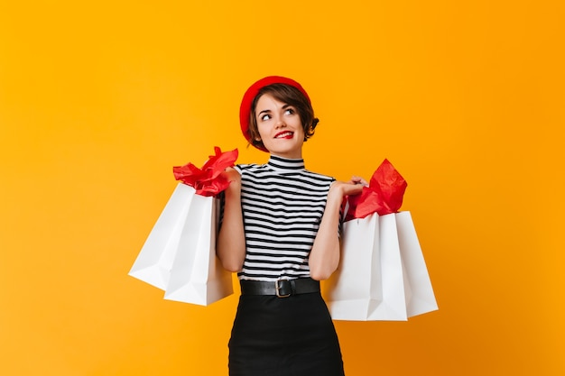 Beautiful woman in stiped t-shirt and red beret holding store bags