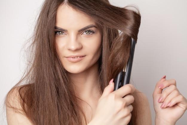 美しい女性は、ヘアアイロンで髪をまっすぐにします。
