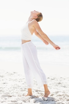 Beautiful woman stretching her arms on the beach