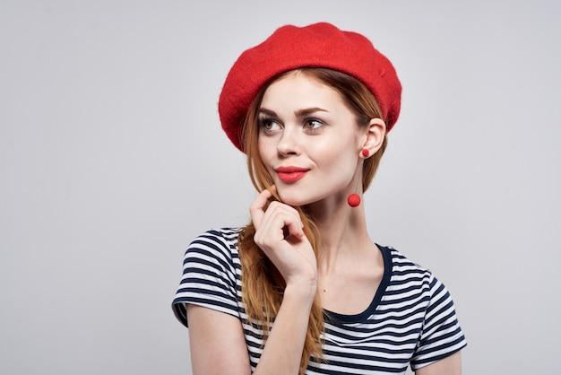 Beautiful woman in a striped tshirt red lips gesture with his hands light background