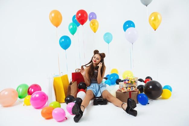 Bella donna accarezzando i capelli durante la ricezione di telefonate per il compleanno