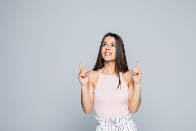 Beautiful woman student raising hands high and pointing up with index fingers isolated on gray wall