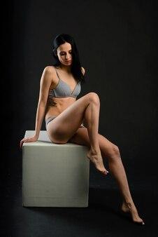 Студийный портрет красивой женщины с татуировкой на черном фоне.
