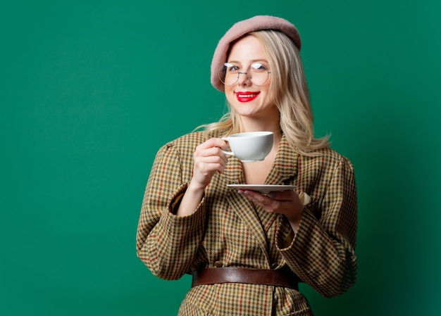 Beautiful woman in style jacket and hat with cup on green wall