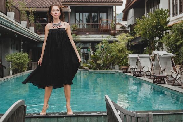 Bella donna in vestito nero lungo alla moda che propone alla piscina della villa tropicale, stile estivo elegante, vacanze, tendenza della moda, camminare a piedi nudi