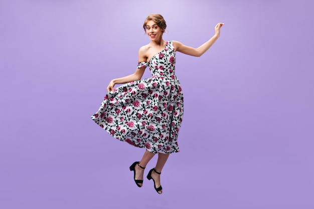 Beautiful woman in stylish outfit jumping on isolated background. pretty young lady in colorful modern clothes and black shoes smiling.