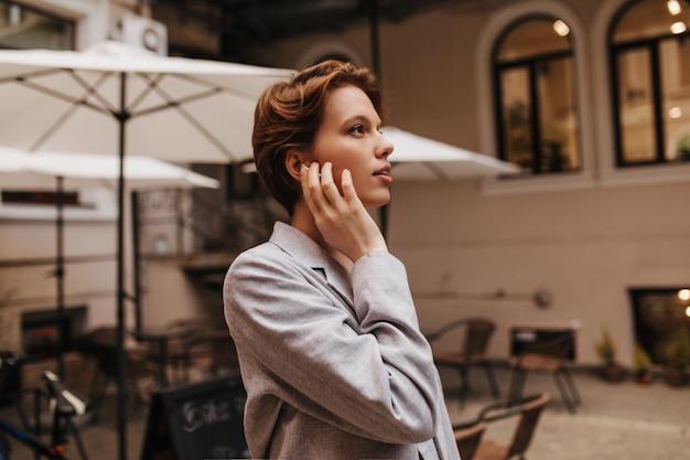 Bella donna in vestito che propone all'esterno. affascinante giovane donna in giacca grigia gode di vista sulla città. ritratto di una ragazza dai capelli corti in street cafe