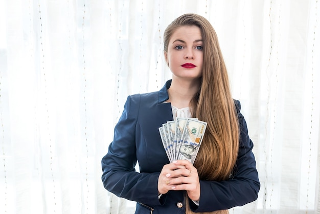 Beautiful woman in suit showing dollar banknotes