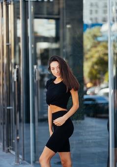 Bella donna, estate in città, allenamento fitness su strada, abbigliamento sportivo.