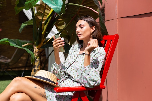 Beautiful woman in summer dress sits on chair in backyard at sunny day with mobile phone