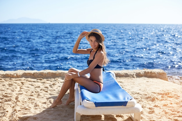 トロピカルトラベルリゾートのビーチで日光浴、夏休みを楽しんでいる美しい女性。