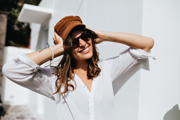 Beautiful woman in sunglasses is wearing corduroy cap. portrait of girl in high spirits against white wall.