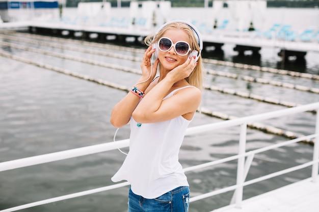 Beautiful woman in sunglasses near river