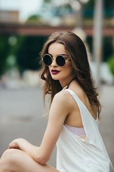Beautiful woman in sunglasses sitting on the asphalt