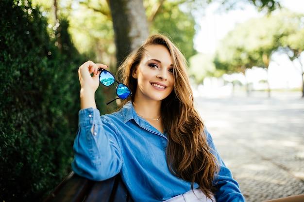 Bella donna in occhiali da sole sorriso rilassante sulla panchina del parco