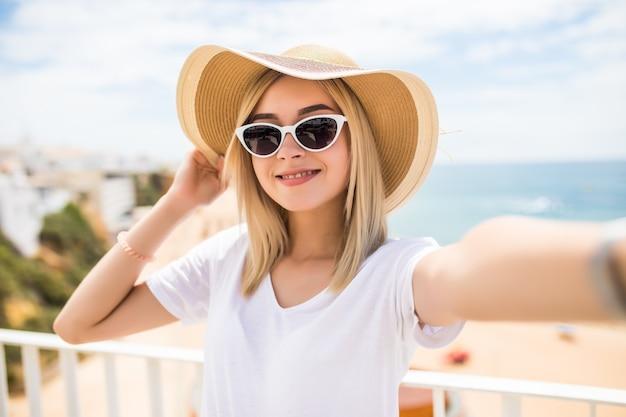 Bella donna in occhiali da sole e cappello estivo prendendo selfie sulla spiaggia