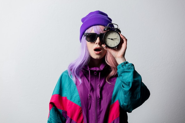 Beautiful woman in sunglasses with alarm clock and 80s sportsuit on white background