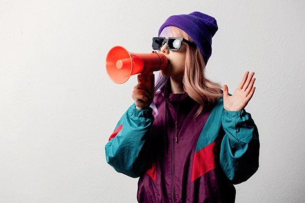 Beautiful woman in sunglasses with bullhorn and 80s sport suit on white background
