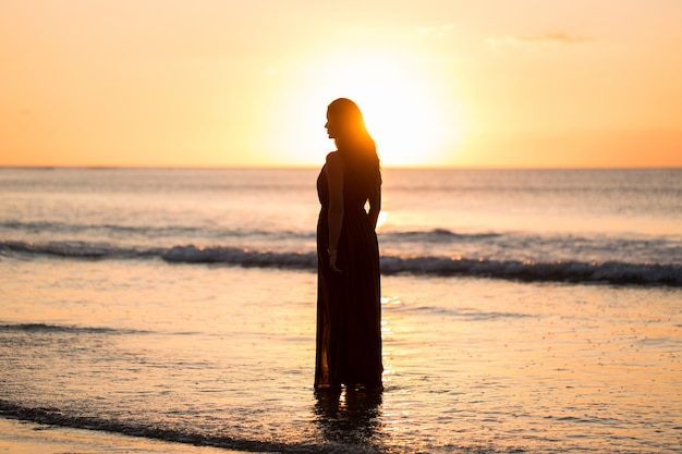 Beautiful woman on sunset. colorful dawn over the sea. carefree woman enjoying the sunset on the beach. happy lifestyle