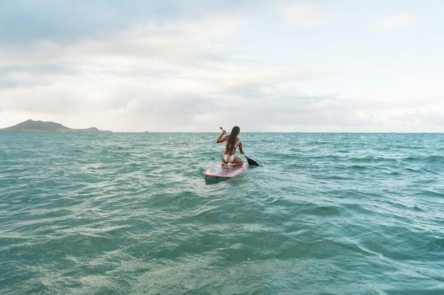 ハワイでサーフィンをする美しい女性