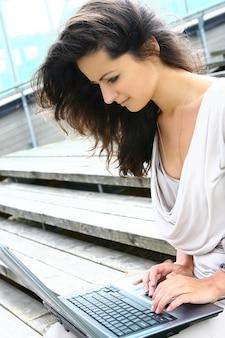 Bella donna che pratica il surfing in internet all'aperto