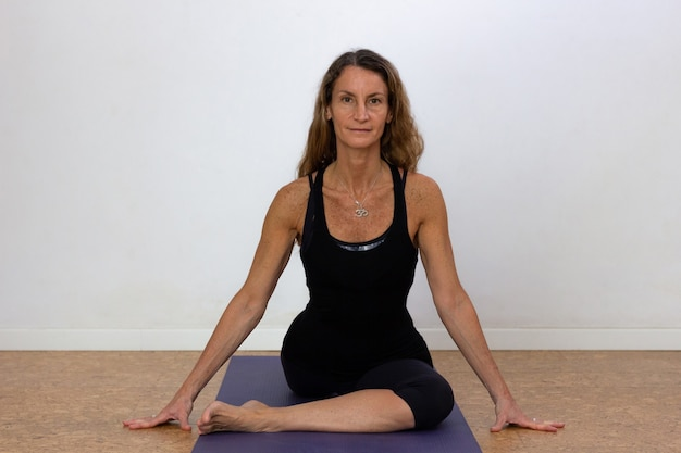Beautiful woman in swan pose on mat over white background slim female yogi on overalls doing yoga
