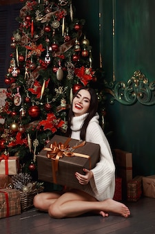 Beautiful woman in sweater holding gifts
