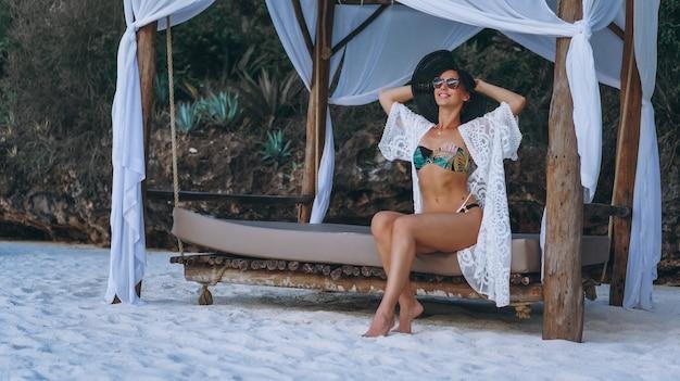 Beautiful woman in swim wear by the ocean