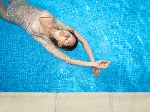 Красивая женщина, плавание в бассейне