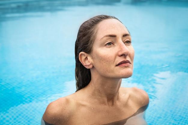 Красивая женщина, плавание голым в бассейне