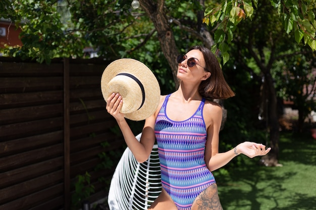 Beautiful woman in swimsuit at backyard at summer sunny day enjoying amazing warm weather, catching sun rays, cheerful happy