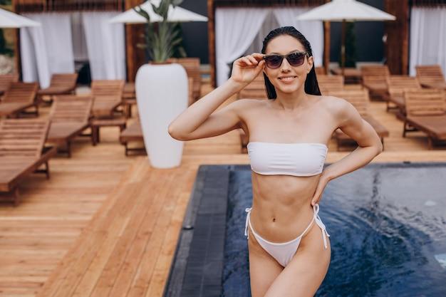 Bella donna in costume da bagno a bordo piscina